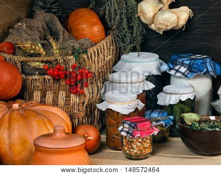 Domestic stocks with marinated vegetables in glass jars on a wooden shelf. Pantry. Pumpkin dishes drawer for vegetables