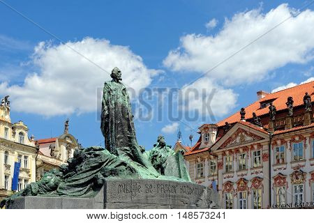 PRAGUE, CZECH REPUBLIC - JULY 3, 2014: The statue of Jan Hus one of the most important personalities in Czech history and the Golz-Kinsky Palace - the National Gallery in Old Town Square.