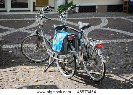 two bycicles standing on the street in the sun
