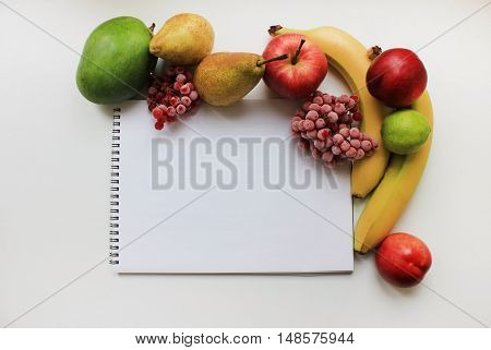 Colorful organic fresh fruit mix and open notebook paper page isolated on white table background. Diet fitness healthy eating food nutrition lifestyle concept with copy space
