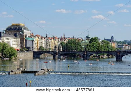View of the Vltava river with many leisure pedal boats from the Charles Bridge. The National theatre and the Legion bridge are seen. Prague Czech Republic.