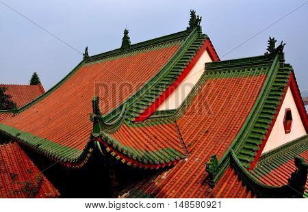 Mianyang China - October 15 2010: Orange tile roofs with green trim and glazed dragons on the lower level dating to 1912 at the Sheng Shui Buddhist Temple