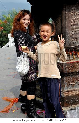 Mianyang China - October 15 2015: Smiling Chinese boy and his mother at the five story paper burner pagoda at the Sheng Shui Buddhist Temple