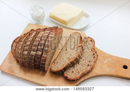 Loaf of freshly baked brown rye wheat whole grain sliced bread on a wooden cutting board with salt and butter isolated on white table background Natural organic food ingredients for sandwich