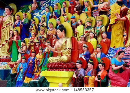 Mianyang China - October 15 2010: Tableaux of hand-painted Buddha figures on a wall at the Sheng Shui Buddhist Temple which dates from the Tang and Qing Dynasties *