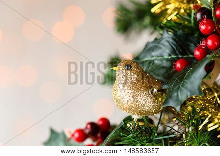 Festive Christmas close up of tree decorated with gold glitter robin tinsel and holly berries. Bokeh copy space.