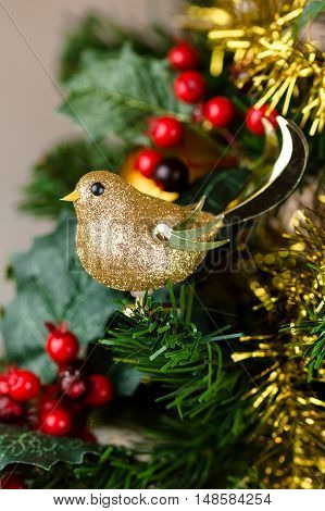 Festive Christmas close up of tree decorated with gold glitter robin tinsel and holly berries. Vertical.