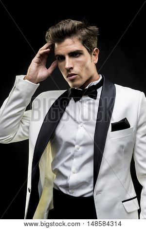 Luxury, elegant man in a white suit tuxedo with bow tie around his neck