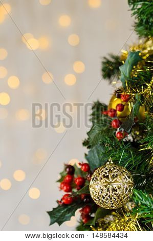 Festive Christmas close up of tree decorated with gold baubles tinsel and holly berries. Bokeh background copy space. Vertical.