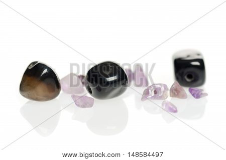 Black and purple gemstones set on a white surface