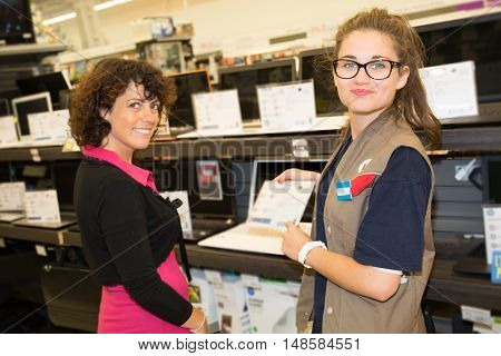 Woman Department Store Choosing Laptop With A Sales Assistant