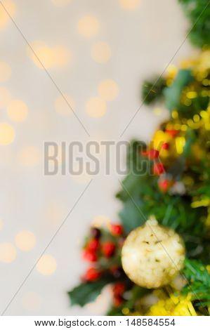 Blurred festive Christmas close up of tree decorated with gold baubles tinsel and holly berries. Bokeh background copy space. Vertical.