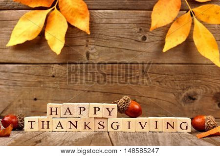 Happy Thanksgiving Wooden Blocks Against A Rustic Wood Background With Acorns And Autumn Leaves