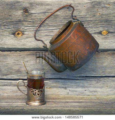 Old copper kettle and cup of tea on a wooden boards background