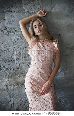 Beautiful young woman posing near wall with her arms akimbo