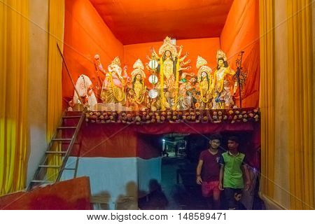 KOLKATA INDIA - OCTOBER 18 2015 : Night image of decorated Durga Puja pandal on upper portion of a narrow street. Editorial image shot at colored light at Kolkata West Bengal India.