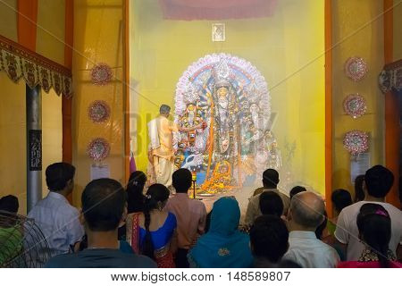 KOLKATA INDIA - OCTOBER 18 2015 : Priest praying to Goddess Durga shot at colored light. It is the biggest religious festival of Hinduism and Bengali Community.