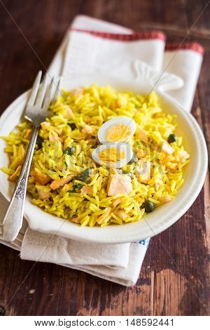 National scottish dish kedgeree with roasted basmati rice, curry powder and fish in a plate, selective focus