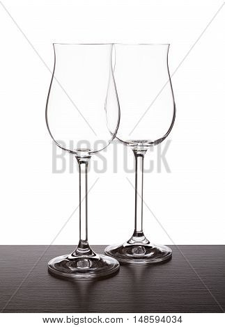 Set of two wine glasses on the table backlight illuminates the silhouette