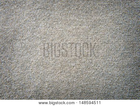 Knitted beige wool fabric into the net with gold thread. Textures, background