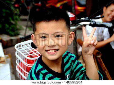 Pengzhou China - October 1 2009: Smiling Chinese boy flashes the