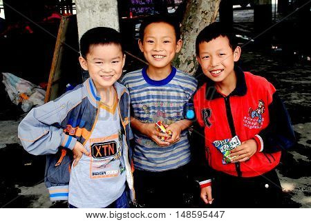 Pengzhou Township China - June 11 2008 Three smiling schoolboys eating packaged food snacks in the Wan Jia village marketplace