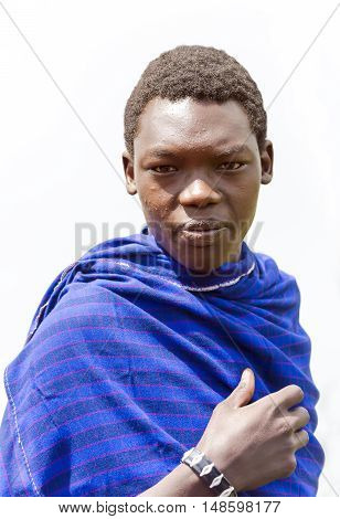 AFRICA, KENYA, MAY, 08, 2016 - Maasai Mara tribe men in a blue cape at Maasai Mara National Park, Kenya, Africa.  The Maasai (sometimes spelled Masai) are a Nilotic ethnic group of semi-nomadic people inhabiting southern Kenya and northern Tanzania.