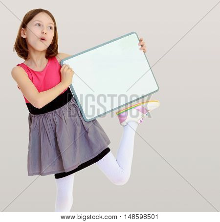 Emotional a small, thin girl, holding a front of a white poster.On a gray background.