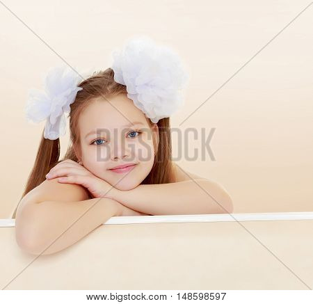 Gentle long-haired little girl with big white bows on the head . She leaned on the windowsill. Close-up.Brown gradient background.
