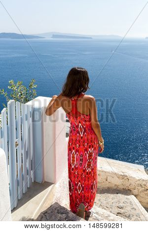Woman in red dress watching the sea at Santorini, Greece