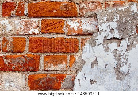 Detail of a wall made of red bricks with plaster. background
