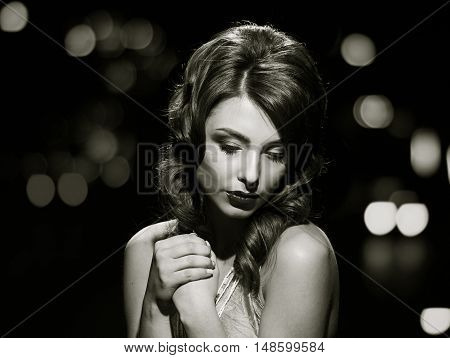 woman studio portrait in hollywood style light on black background with night lights city background. in black and white toning