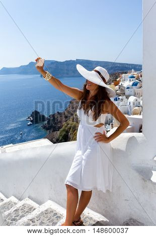 Woman in white dress is taking a selfie at the village of Oia, Santorini