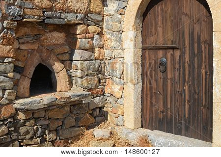 Closed wooden door and the stone wall with small window