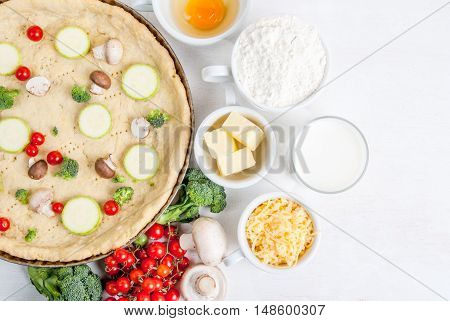 The selection of ingredients for the preparation of traditional French dishes quiche lorraine, on white wooden table with a baked dough in the baking dish in the cooking process, top view, copy space