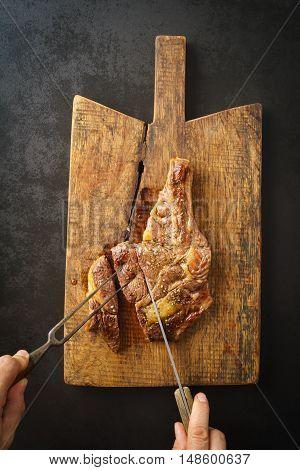 Man cutting a seared dry aged rib eye steak