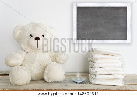 A teddy bear on a wooden table next to a pacifier and some diapers. A blackboard with empty copy space for Author's text.
