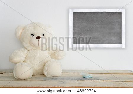 A teddy bear on a wooden table next to a pacifier. A blackboard with empty copy space for Author's text.