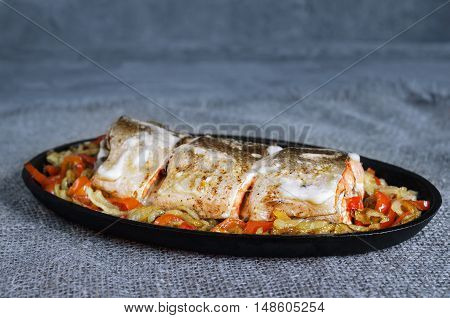 Salmon baked in mayonnaise with vegetables in a cast iron skillet and a gray-blue background. Rustic style
