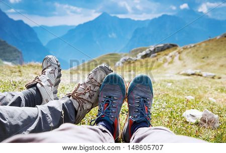 Couple in hiking boots on the background of mountains. Family on trekking day in the mountains. Mangart Julian Alps National Park Slovenia Europe. Travel Lifestyle Concept.
