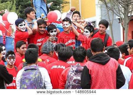Cajamarca Peru - September 23 2016: Young men dressed in red ride truck in Carnival parade in Cajamarca Peru on September 23 2016