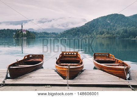 Traditional wooden boats on the backgorund of Church on the Island on Lake Bled Slovenia. Amazing View On Bled Lake. Autumn time in Slovenia Europe.