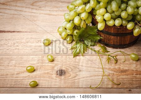 Green grapes with leaf at wooden board in rustic style