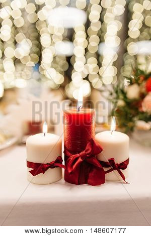 Three decorative candles burning on the table