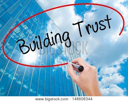 Man Hand Writing Building Trust With Black Marker On Visual Screen