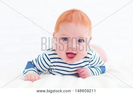 Portrait Of Happy Redhead Baby Boy Lying On Belly