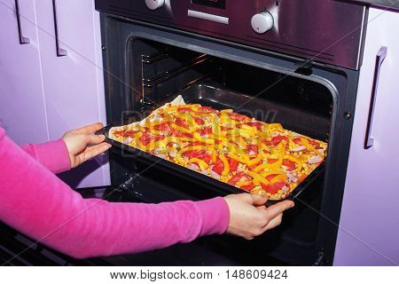 The woman pushed the pizza in the oven. The concept of cooking.
