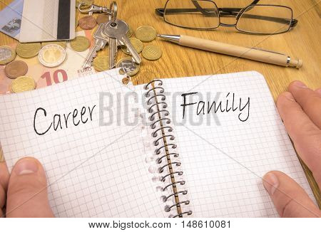 Family over career concept - Conceptual image depicting choosing family over career. A man's hands tears a notebook page with the word career. There are financial elements in the background