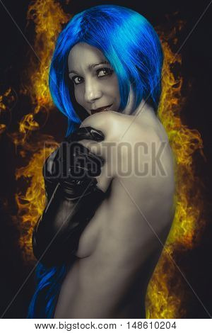 vogue style portrait of beautiful delicate woman with blue hair over fire flames