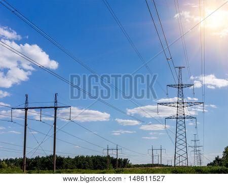 Electricity pylons and lines at sunset rays of sunlight